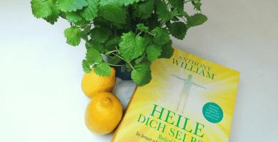 Es zeigt das Buch von Anthony Williams, Heile dich selbst dekoriert mit zwei Zitronen und einem grünen Kräutertopf. In diesem Buch ist die Leberreinigung ausführlich beschrieben.