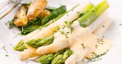 man sieht gekochte grüne und weisse Spargeln mit einer weissen Sauce darüber und ein paar Kräuter darübergestreut. Hinter den Spargeln sind noch zwei Kartoffelhälften zu sehen. Der Teller ist weiss.