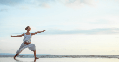 man sieht eine Frau in Yogaposition am Strand am Meer
