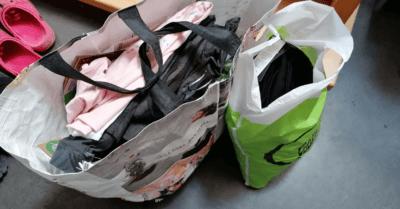 Man sieht zwei Einkaufstaschen mit Kleidern drin.