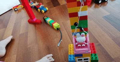 man sieht verschiedene Legosachen, die gebaut wurden und den Teil eines Kinderfusses. Alles steht auf einem Holz-Parkettboden.