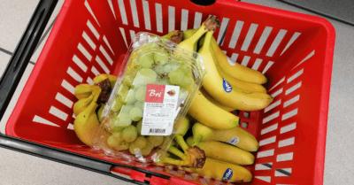 man sieht viele Bananen und eine Schachtel Trauben in einem roten Einkaufskorb.