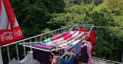 Man sieht einen Wäscheständer mit bunten Kleidern. Im Hintergrund sieht man viele grüne Bäume. Die Wäsche ist auf einem Balkon aufgehängt. Da steht ein Coca-Cola-Sonnenschirm.