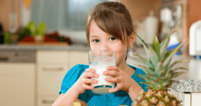 man sieht ein Mädchen mit einem blauen T-Shirt in einer Küche stehen vor einer Ananas. Sie trinkt ein Glas Milch. Ist Milch gesund für unsere Knochen?