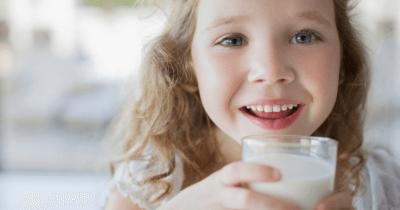 Man sieht ein Mädchen, das gleich ein Glas Milch trinken wird. Ist die Milch gesund für unsere Knochen?Sie lacht. Der Hintergrund ist verschwommen!