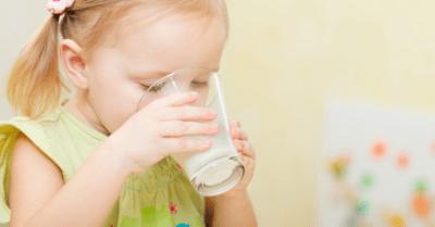 Man sieht ein Mädchen mit grünem Kleid, das ein Glas Milch trinkt. Der Hintergrund ist gelblich.