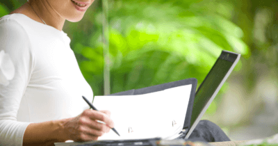 eine Frau schreibt auf ein Blatt Papier. Sie hat einen Stift in der Hand und auf den Knien einen Laptop. Im Hintergrund sieht man grün. Den Kopf der Frau sieht man nicht, nur dass sie lacht.