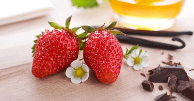 Man sieht zwei Erdbeeren. Weisse Erdbeerenblüten auf einem Holztisch. Zwei Vanilleschoten und etwas geraspelte Schokolade.