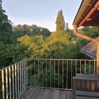 Man sieht einen Balkon mit Holzboden. Die Aussicht ist auf Bäume. Ein wunderschöner Morgen am 12. Juni 2021, das ist das erste Foto von 12 von 12.