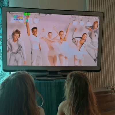 Man sieht tanzende junge Menschen auf einem TV-Bildschirm. Davor sitzen zwei Mädchen mit langen Haaren.