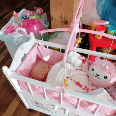Man sieht einen rosa Puppenecken mit Wickeltisch und Bettchen.