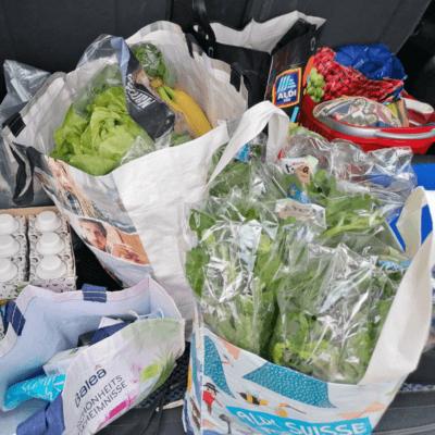Man sieht Einkaufstaschen, die im Kofferraum stehen. Voll mit Gemüse, Salat, Früchten. Dieser Einkauf wurde am 12. Juni 2021 gemacht. Das ist das 6. Bild für 12 von 12.