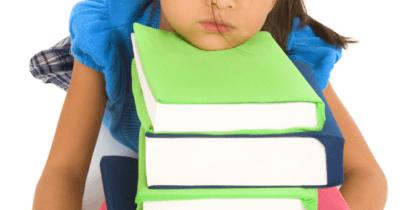 Man sieht ein Kind mit einer blauen Bluse, den Kopf lustlos auf einen Stapel Bücher legen.