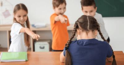 Man sieht Schüler, die mit dem Finger auf eine Schülerin zeigen und sie auslachen. Die Schülerin hat den Kopf gesenkt.