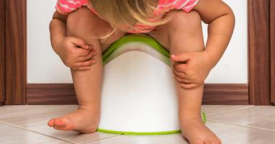 Man sieht ein Kind auf einem weissen Topf mit grünem Rand sitzen. Es ist nach vorne geneigt.