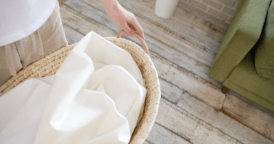 Man sieht jemanden einen Wäschekorb mit weisser Wäsche tragen. Der Boden ist aus Holz. Wäsche machen gehört nicht zur Lieblings-Tätigkeit als Lymph-Massage-Therapeutin.