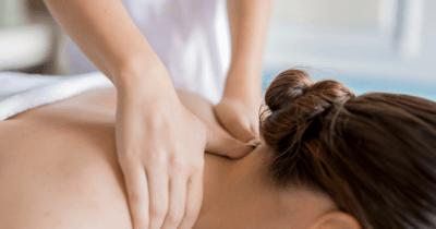Man sieht, wie man den Nacken einer Frau massiert. Es sind nur Hände, Nacken und der Hinterkopf zu sehen bei der Tätigkeit als Lymph-Massage-Therapeutin.
