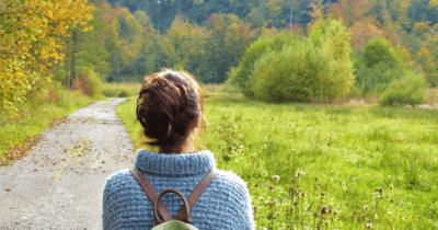 Man sieht eine Frau in der Natur einen Weg entlang gehen. Im Hintergrund sind viele grüne und gelb blühende Sträucher zu sehen.
