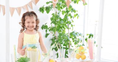 Man sieht ein Mädchen vor einem Krug mit Zitronenwasser und auf dem Tisch vor ihr sind Zitronen, Gläser und Wasser. Hinter ihr sieht man eine Partydekoration und einen grünen Zimmerbaum.
