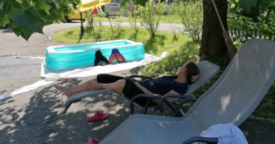 Man sieht einen Swimminpool, Sonnenschirm, Liegestühle und Jeannine liegt auf einem Liegestuhl.