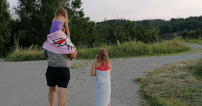 Man sieht einen Mann, ein Kind auf den Schultern und ein Mädchen in Badehosen, mit Tuch einen Feldweg entlang spazieren.