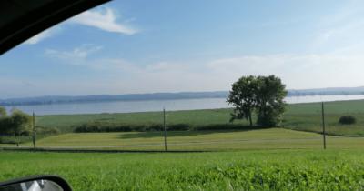 Man sieht grüne Wiese, einen Streifen See und im Hintergrund wieder einen Streifen Land