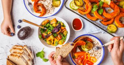 Man sieht Gericht mit viel Gemüse, orangem Kürbis, Reis und Brot.