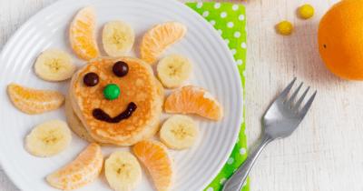Man sieht einen Teller mit einem Pancake mit Schokogesicht in der Mitte und Bananen, Mandarinen abwechselnd als Strahlen. Daneben liegt eine Gabel und eine Mandarine. Bananen sind sehr gesund und machen gute Laune.