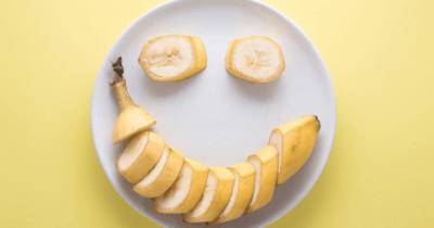 Man sieht einen weissen Teller mit einer aufgeschnittenen Banane. Mit der Banane wurde ein lachender Mund und zwei Augen geformt. Der Untergrund ist gelb. Bananen sind gesund.