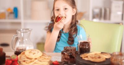 Man sieht ein Mädchen mit langen braunen Haaren und einem blauen Shirt. Sie beisst in ein Stück Brot mit Nutella drauf. Vor ihr lieben Pancakes, Nutellagläser und ein Krug mit Milch.