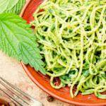 Man sieht einen orangen Teller voll Nudeln mit Pesto. Brennessel-Samen sammeln, trocknen, Anwendung erfährst du hier.