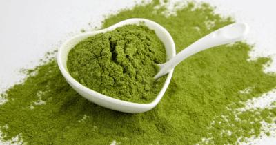 man sieht grünes Gerstengrassaftpulver auf weissem Hintergrund. In einem weissen Herzschälchen ist dieses grüne Pulver auch. Darin ist ein weisser Löffel.
