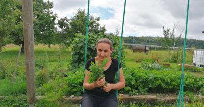 Man sieht Jeannine auf einer Schaukel sitzen mit einem Bündel Kräuter in der Hand. Im Hintergrund ist eine grüne Wiese, ein Garten und Bäume zu sehen.