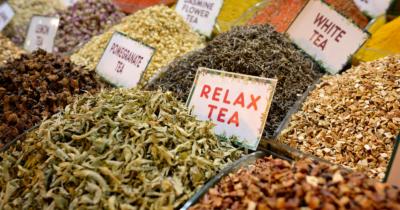 """Man sieht viele verschiedene Kräuter auf einer Verkaufsauslage. Sie sind angeschrieben mit Täfelchen """"Relaxtea, White Tea usw. Kräuter sind mein Hobby."""