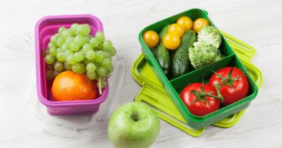 Man sieht eine pinke Znünibox mit Trauben und Orangen, einen grünen Apfel daneben und eine grüne Znünibox mit Tomaten, Gurken, gelben Tomätli und zwei Brokkoliröschchen. Das sind alles wunderbare Lebensmittel um die Leber natürlich entgiften zu können.
