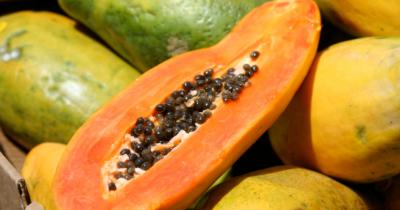 Man sieht Papayas und eine halbierte orangefleischige Papaya aufeinander.