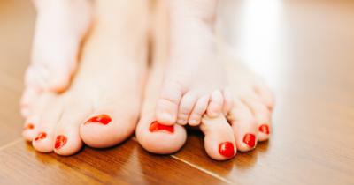 Man sieht gepflegte Füsse mit roten Nägeln. Zwei Kinderfüsse stehen auf den Frauen-Füssen.