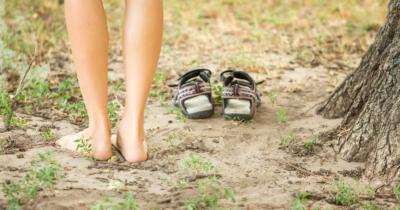 Man sieht zwei nackte Beine, die Barfuss auf dem sandigen, etwas grünen Boden stehen, neben einem Baum. Die Schuhe stehen nebendran.