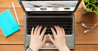 Man sieht einen Laptop und zwei Hände über der Tastatur. Ein türkis Notizbuch und Bleistift, weisse Kopfhörer und eine grüne Pflanze sind zu sehen. Das ist alles nötig für meine Sommer Business Pläne 2021