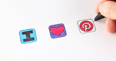 man sieht drei gezeichnete Symbole. Ein blaues Quadrat mit einem grossen schwarzen I, ein lila Quadrat mit einem Roten Herz, ein weisses Quadrat mit einem schwarzen Rand und das rote Pinterest Zeichen. Dann sieht man noch einen schwarzen Stift und Finger, die gerade am Pinterest-Zeichen zeichnen sind.