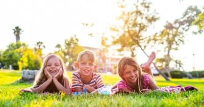 Man sieht drei Kinder fröhlich bäuchlings im Gras liegen. Im Hintergrund sieht man eine Wiese und etwas Haus.
