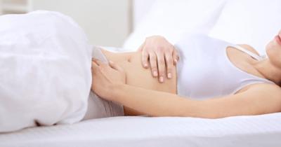Man sieht eine Frau in einem weissen Bett liegen. Der Kopf ist nicht sichtbar. Sie hält eine Hand auf ihren Bauch. Auch im Monatsrückblick Juli 2021 ist Bauchweh nach dem Essen ein Thema.