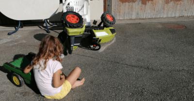 Man sieht einen umgestürzten Kindertraktor und ein 6jähriges Kind, dass auf den Traktor schaut. Sie sitzt draussen auf dem Vorplatz und stützt sich auf den grünen Anhänger des Traktors.