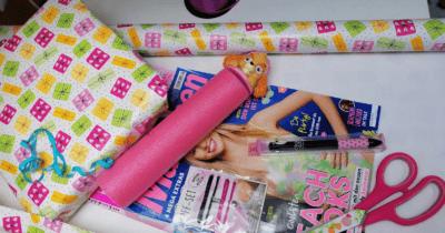 Man sieht zwei Mädchenzeitschriften, eine pinke Paw Patrol Wasserpistole, eine pinke Schere und Geschenkpapier in pink, rosa, gelb, weiss, grün auf weissem Untergrund.
