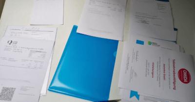 Man sieht ein blaues Mäppli und rundherum liegen viele Blätter, Bescheinigungen, Rechnung, Zertifikate für Weiterbildungen von Jeannine.
