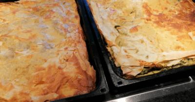 Man sieht zwei Backbleche voll Pite. Einmal mit Fleisch, einmal mit Spinatfüllung.