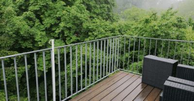 Man sieht eine verregnete Terrasse und gründe Bäume im Hintergrund