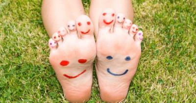 Man sieht zwei Kinderfüsse. Der eine hat ein rotes lächelndes Gesicht auf die Fusssohle und die Zehen gemalt, der andere ein blaues lachendes Gesicht. Die grossen Zehen haben jeweils rote Gesichter. Die Füsse liegen im Gras.