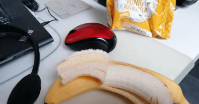 Man sieht eine Computermaus, eine angebissene Banane, ein gelbes Papier von Reiswaffeln.
