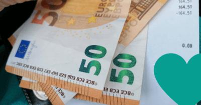 Man sieht 3 50-er Euro Noten neben einer Post-Quittung. Rechts unten ist ein Stück von einem türkis Herz zu sehen.